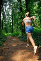 Lady enjoying running on forest trail with more energy